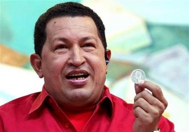 Hugo Chavez holds up a bolivar coin